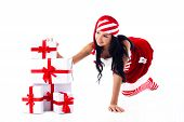 Santa Girl Is Sitting On Its Hands On A Pile Of Gifts. Holidays Christmas And New Year.