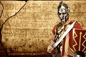 stock photo of legion  - Roman legionary soldier in front of abstract wall - JPG