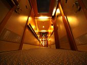 Narrow And Long Illuminated Corridor With Hotel Rooms In Cruise Ship