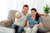Happy Man Watching Television With His Girlfriend Sitting On The Sofa