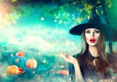 Halloween Witch pointing hand over dark magic field with  Pumpkins and magic lights in forest. Beaut poster