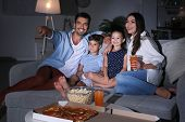 Happy family watching TV on sofa at night poster