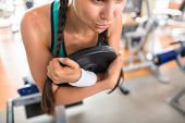 Close-up shot of exhausted sporty woman dripping with sweat having intensive workout at modern gym,  poster
