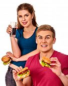 Couple eating fast food. Man and woman treat big hamburger with ham. Friends give burder junk on whi poster