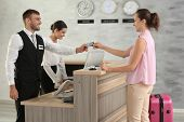 Woman paying for hotel room at reception poster