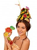 Girl drinking fruit cocktail on summer party. Woman with fresh fruits hairstyle and bare back hold h poster