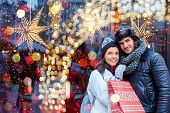 Christmas shopping together. Young happy couple doing christmas shopping. Christmas lights in the ba poster
