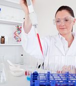 Cute Female Biologist Holding A Manual Pipette With Sample From Test Tubes