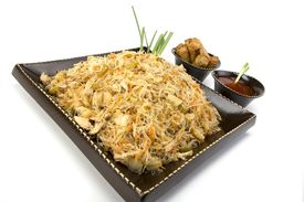 picture of lumpia  - Pancit on a ceramic dish with egg rolls and sweet and sour sauce - JPG