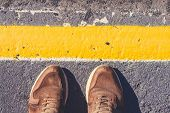 A Person Is Standing Next To The Yellow Line Drawn. Shoes Stoin On The Pavement Gray Shade. poster