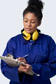 Studio Shot Of Female Engineer With Clipboard And Spanner Against White Background poster