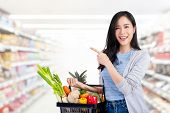 Beautiful Asian Woman Holding Shopping Basket Full Of Vegetables And Groceries In Supermarket Pointi poster