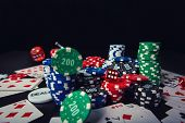 Close Up Stack Of Different Colored Poker Chips, Playing Cards And Dices Isolated Over Black Casino  poster