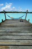 Hammock swinging in a pier by a tropical landscape, with a side table laden with fruits and refreshments