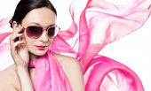 Beautiful woman in pink silk scarf wearing sunglasses