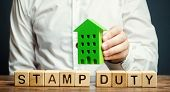 Businessman And Wooden Blocks With The Word Stamp Duty And House. Taxes Assessed During The Transfer poster
