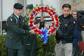 NEW YORK - NOVEMBER 11: NYC Councilman John Liu (R) helps a U.S. soldier carry a wreath at a Veteran's Day Memorial service at St. John's University November 11, 2005 in Queens, NY.