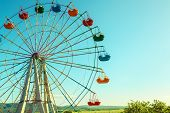 Scenic View Of Ferris Wheel In Amusement Park. Colorful Ferris Wheel On The Blue Sky Background. Bea poster