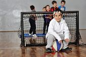 Young boy sitting on basketball,soccer goal and his friends in background