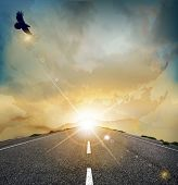 landscape with rising sun, soaring eagle, and the road