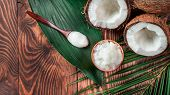 Top View Of Coconut Mct Oil In Bowl And In Spoon And Halved Coco-nut On Wooden Table. Health Benefit poster
