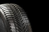 stock photo of four-wheel drive  - Part of new winter automobile car tyre on black backgroung - JPG