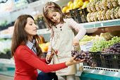 Compras de comida familiar. Madre de joven y pequeña hija chica elegir frutas uvas en supermercados