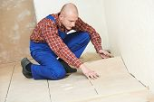 stock photo of overhauling  - professional tiler builder worker installing home floor tile at repair renovation work - JPG