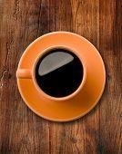 Café preto em uma vista superior do copo laranja com fundo de mesa de madeira