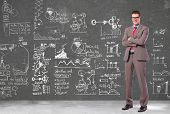 confident business man with glasses standing with arms crossed n front of a wall filled with calcula