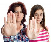 stock photo of gender  - Young latin woman and a teenage girl signaling to stop with their hands extended isolated on white  - JPG
