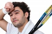 picture of transpiration  - Tennis player wiping the sweat from his brow - JPG