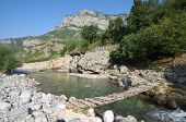 small wooden bridge on a tributary creek of Cemi River in Commune Kelmend, Albania