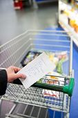 Hand, holding a shopping list with day to day groceries and other necessities, whilst pushing a shop