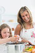 Lachen, Mutter und Tochter vorbereiten Gemüse und setzen sie in großen Topf