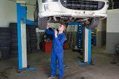 Male mechanic working under raised car in garage