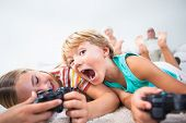 Brother and sister playing video games and having fun on the floor