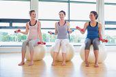 Três mulheres na ginástica com halteres e bolas de exercício