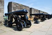 stock photo of cannon  - A row of vintage cannon behind parapet wall - JPG