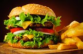 stock photo of junk  - closeup of traditional cheeseburger or hamburger and frech fries - JPG