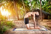 stock photo of beach hut  - Yoga ushtrasana camel pose by fit man with dreadlocks on the beach near the fishermen hut in Varkala Kerala India - JPG