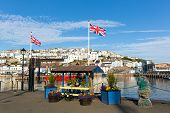 Colourful flowers and union jack flags at harbourside Brixham harbour Devon with blue sky
