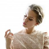 Girl with perfume, young beautiful woman holding bottle of perfume and smelling aroma, isolated on white background