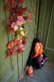 Portrait of Halloween girl with red hair sitting on the porch of dilapidated house