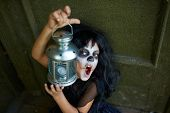 picture of antichrist  - Portrait of Halloween girl with lantern looking at camera with frightening expression - JPG