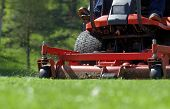 stock photo of grass-cutter  - view of a riding mower in action - JPG