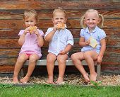 Children eating on the rural bench.