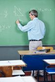Rear view of male professor solving mathematics on greenboard in classroom