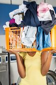 Young woman carrying basket of dirty clothes in front of her face at laundromat