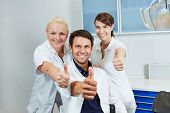 Happy dentist and smiling dental team holding their thumbs up in dental practice